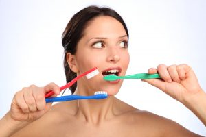 Fun young woman with three toothbrushes